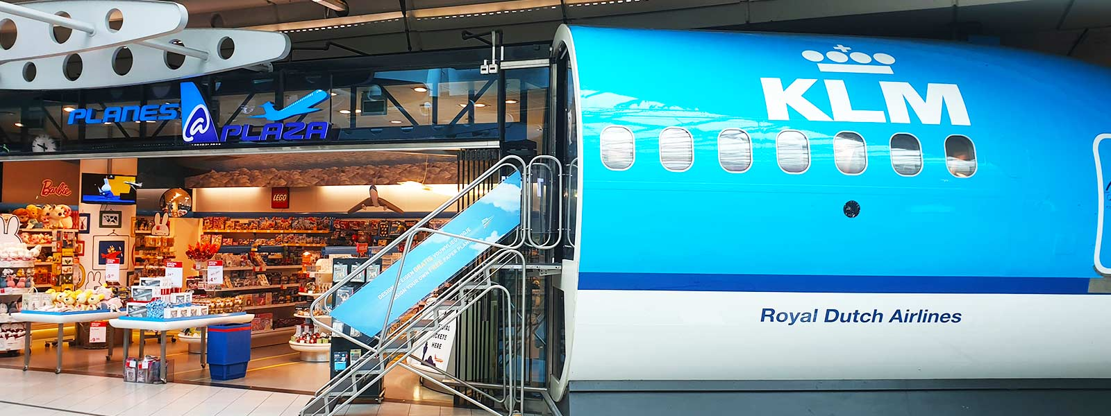 Stuk KLM toestel bij de souvenirwinkel