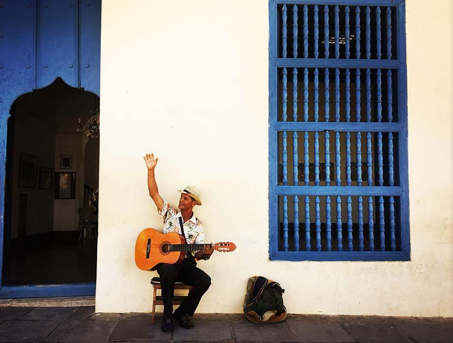 Een inwoner in Cuba met gitaar voor een gebouw