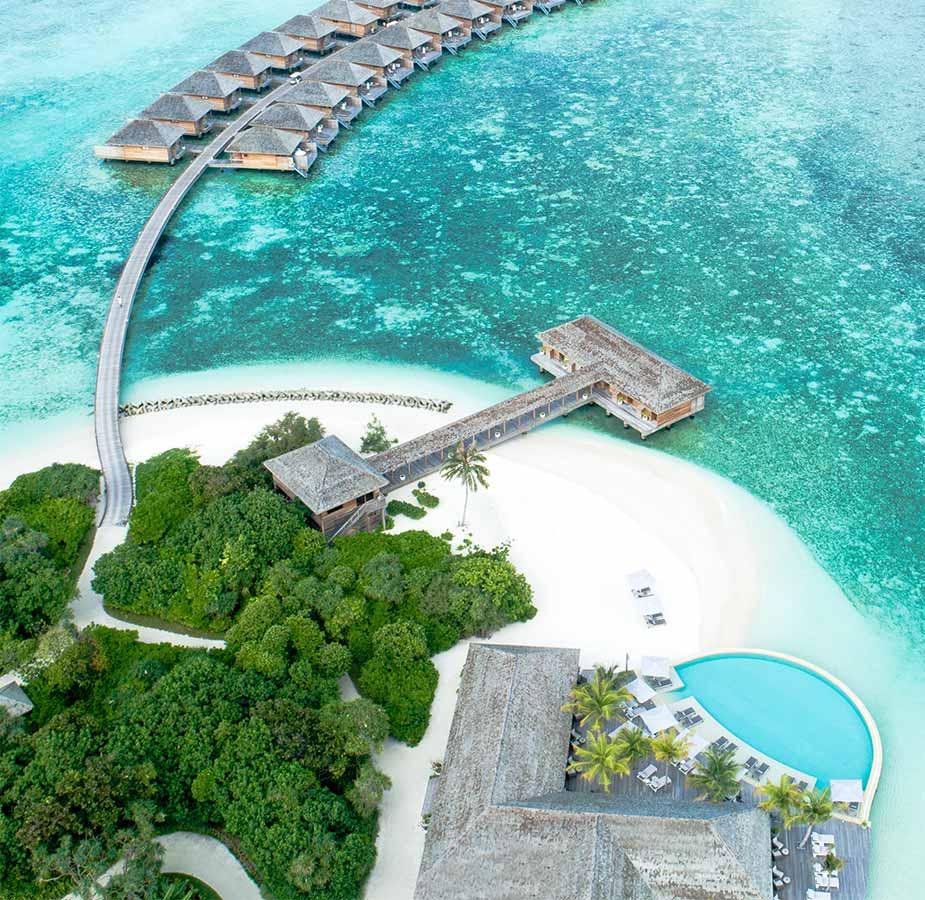 Strand en bungalows in het water bij Hurawalhi Maldives Resort