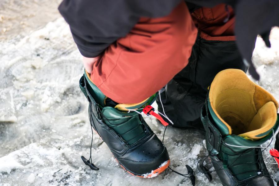 Snowboard schoenen aantrekken op wintersport.