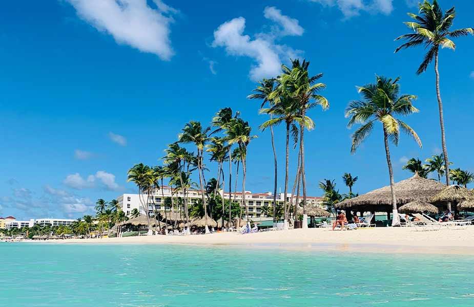 Strand op Aruba met blauwe zee en palmbomen