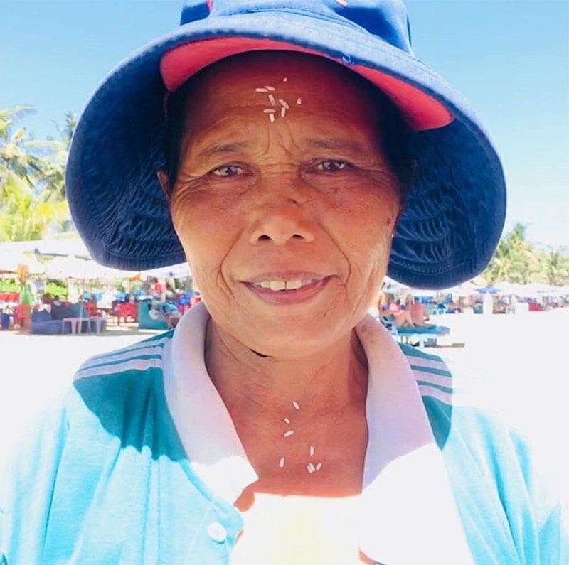 Vrouw op Bali met rijstkorrels in gezicht
