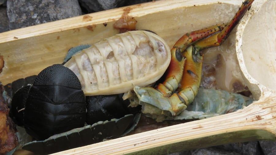Traditioneel eten Polynesische locals van krab, varkensvlees, broodvrucht en schaaldieren