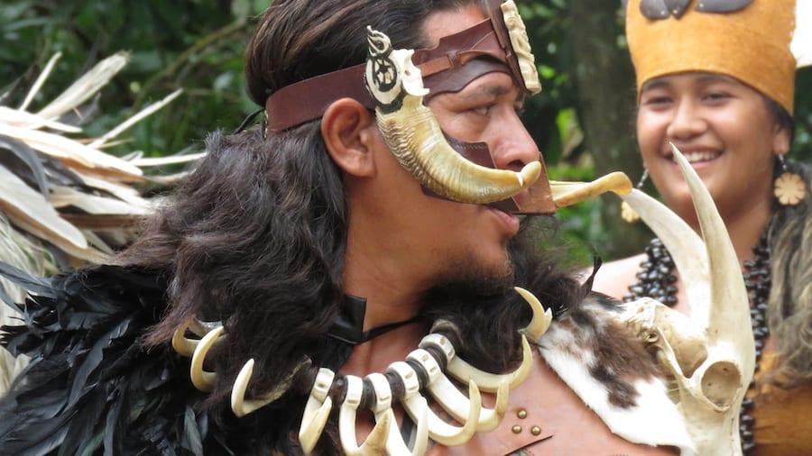 Polynesische man in traditionele kledij tijdens de haka dans