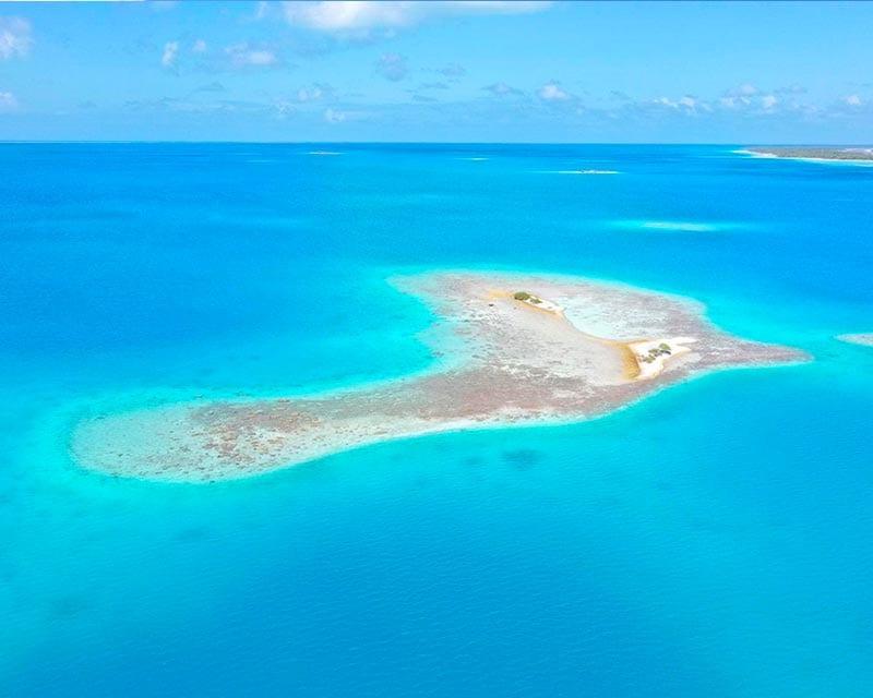 Eilandje en blauwe zee Tuamotu archipel
