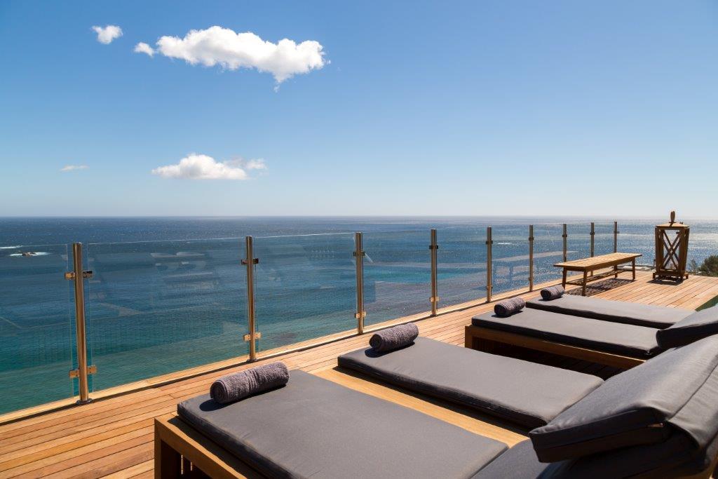 Ligstoelen bij zwembad met fantastisch uitzicht over zee