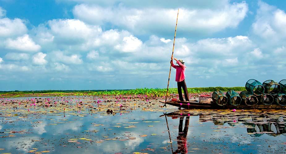 Een visser op zijn boot in Thale Noi
