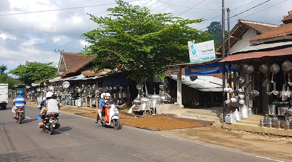 Straatbeeld in Kalibaru met veel handelswaar bij de winkels
