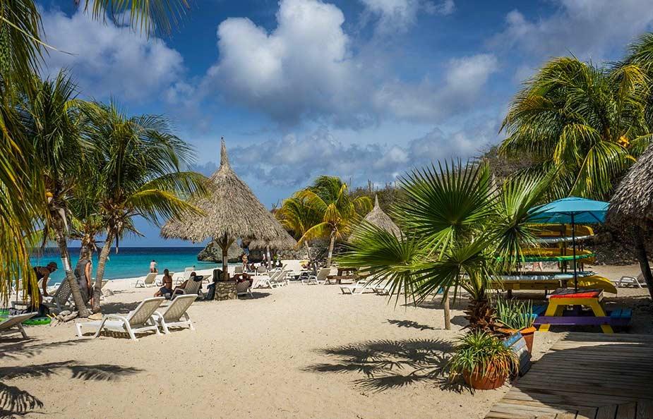Strand met palbomen en ligbedden op Curacao