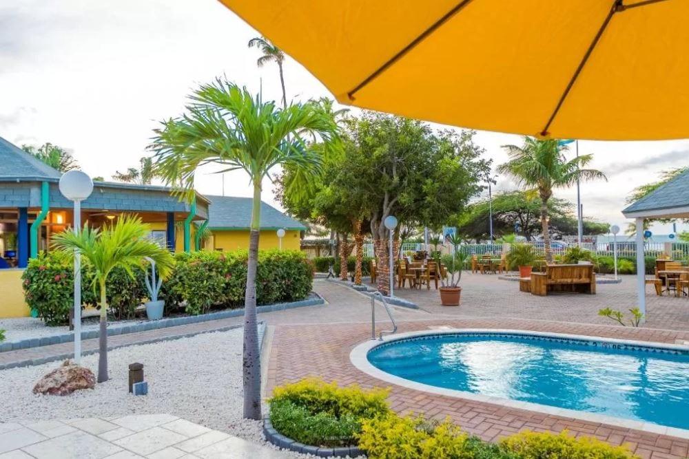 Het zwembad met tuin, zitje en parasols
