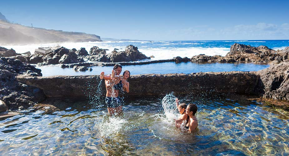 Kinderen spelen in een natuurlijk zwembad bij Garachico
