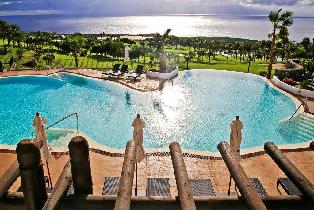 Uitzicht vanaf terras over zwembad en golfterrein