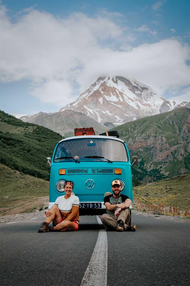 Milene en Yuri voor de bus met op de achtergrond bergen