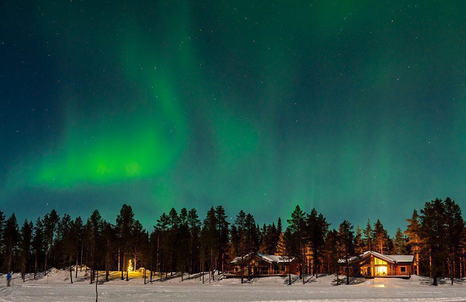 Het noorderlicht boven hutjes in Lapland
